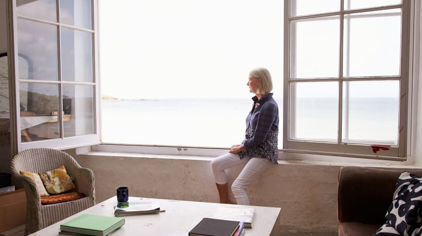 Woman Sitting At Window And Looking At Beautiful Beach View. Wie will ich im alter wohnen?