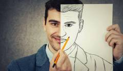 Portrait of a smiling businessman hiding half face with a white empty paper, drawing his real angry emotion. Create new identity, grey wall background.
